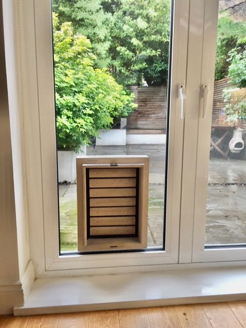 Dog Flap | Cat Flap | Dog Door | Cat Door | Bouncer (Large) Grey wooden dog flap for a Boxer and cat door installed in a double glazed window with aluminium profiles | © Tomsgates